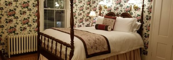bedroom with floral wallpaper, burgundy accents and 4-poster bed