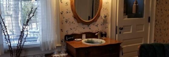 room with fancy sink set in dresser with mirror above