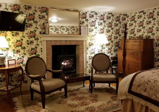 bedroom with floral wallpaper, burgundy accents and 4-poster bed, with chairs next to blazing fireplace