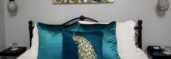 picture over bed decorated in aqua pillows