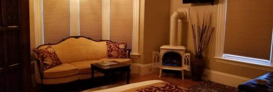 Bette Davis room with corner fireplace, sofa and burgundy and gold accents