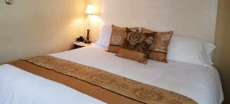 bed with white bedspread, decorated with brown accents and dramatic headboard