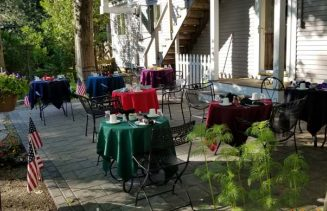 back patio area with tables with multicolored tablecloths, set for a meal