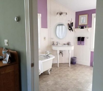 bathroom with pedestal sink and clawfoot tub decorated with purple accents