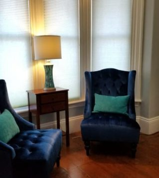 two dark blue chairs set in bay window, with lamp inbetween and mirror to the side